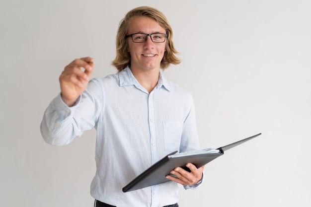 Cartella sorridente della tenuta del giovane tipo e scrittura in aria Foto Gratuite