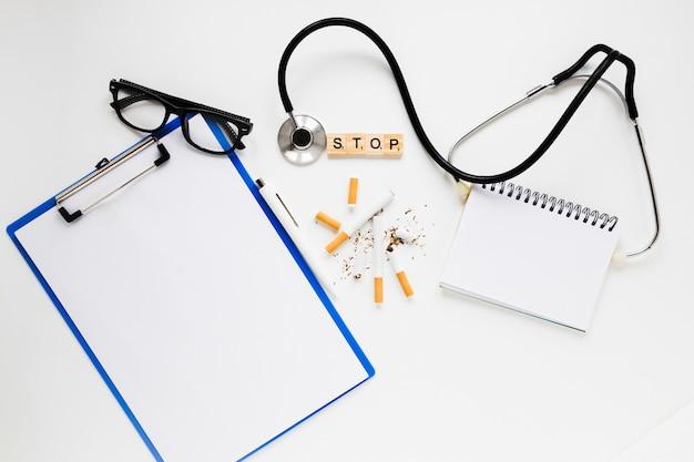 Cartella vista dall'alto con sigarette e stetoscopio Foto Gratuite