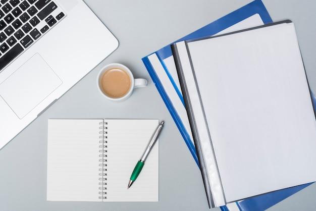 Cartelle aziendali con tazza di caffè; laptop e blocco note a spirale aperta; penna sul tavolo grigio Foto Gratuite