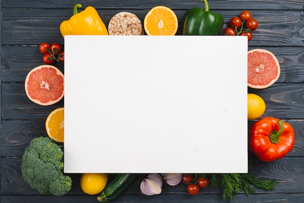 Cartello bianco sopra le verdure colorate sul tavolo di legno nero Foto Gratuite