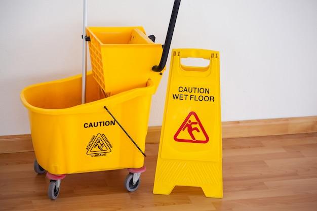 Cartello cartello giallo con secchio scopa sul pavimento contro il muro Foto Premium