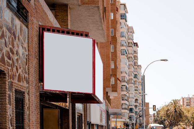 Cartellone bianco all'esterno dell'edificio in città Foto Gratuite