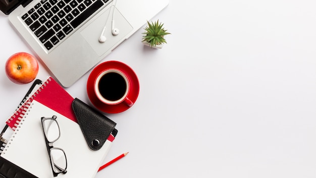 Cartoleria, occhiali da vista, mela, laptop, auricolari e pianta di cactus sulla scrivania Foto Gratuite