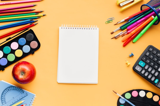 Cartoleria scuola multicolore sparsi attorno al blocco note in bianco sulla scrivania gialla Foto Gratuite