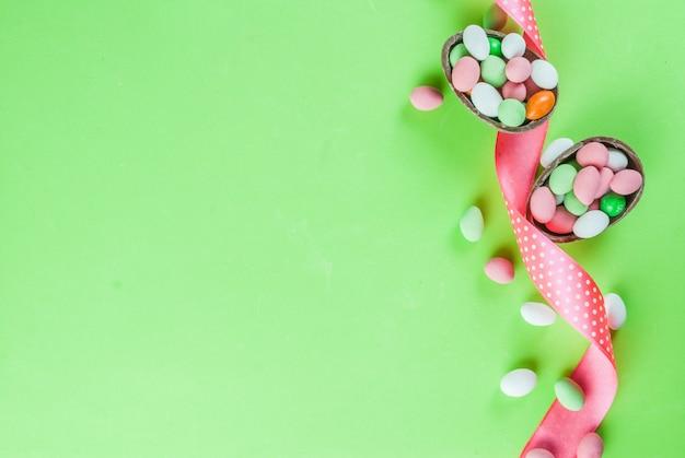 Cartolina d'auguri di festa di pasqua, con coniglietto di pasqua al cioccolato, uova di caramella, uova di quaglia e nastro festivo, vista dall'alto Foto Premium