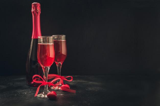 Cartolina d'auguri di san valentino e compleanno con champagne e caramelle cuore nero. Foto Premium