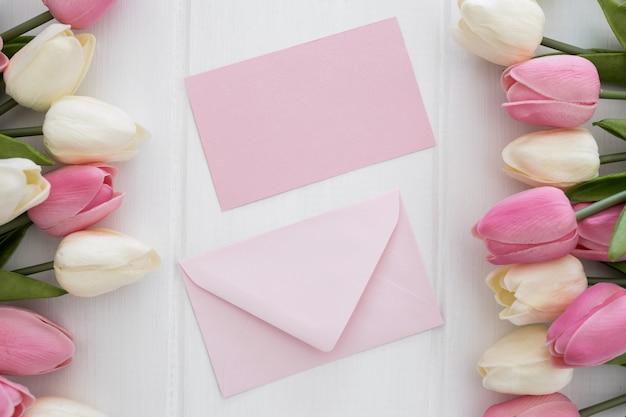 Cartolina d'auguri e busta adorabili con i fiori dei tulipani su fondo di legno bianco Foto Gratuite