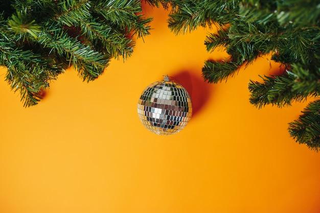 Cartolina di natale con copyspace. palla da discoteca in argento con rami di abete intorno. Foto Premium
