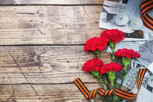 Cartolina può 9 - garofani rossi nastro george vecchie foto su uno sfondo in legno. Foto Premium