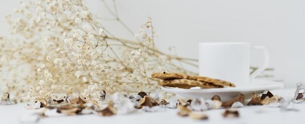 Casa accogliente con una tazza di caffè e ramo di fiori. hygge stile invernale o autunnale Foto Premium