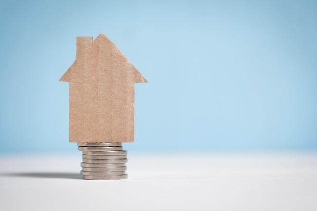 Casa astratta del cartone su una pila di monete. Foto Premium