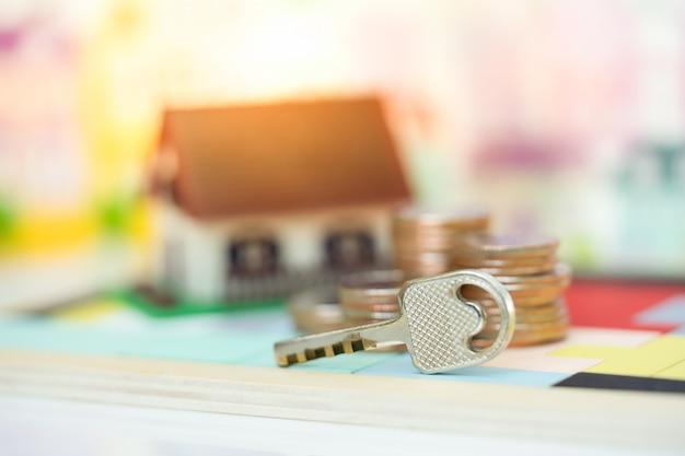 Casa chiave e modello di casa come sfondo. concetto per la scala di proprietà, l'ipoteca e l'investimento immobiliare. Foto Premium