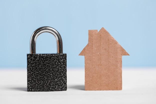 Casa del ritaglio del cartone e lucchetto nero su blu e bianco. Foto Premium