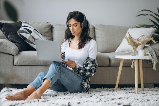 Casa di seduta della giovane bella donna che lavora al computer portatile in cuffie Foto Gratuite