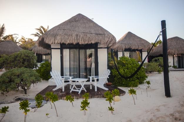 Casa di spiaggia tropicale sulla riva dell'oceano tra le palme Foto Premium