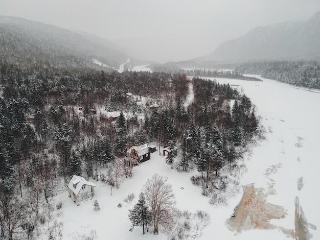 Casa marrone su terreno innevato circondato da alberi Foto Gratuite