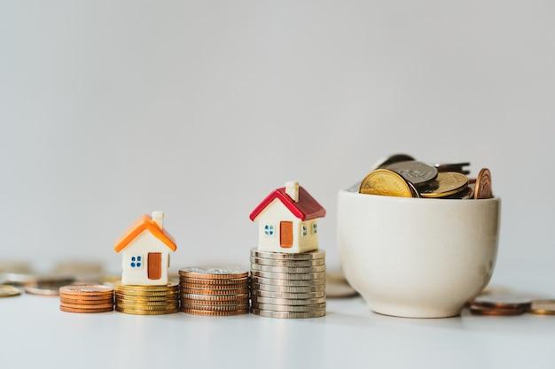 Casa miniatura sul mucchio delle monete con le monete piene in tazza facendo uso di bene immobile della proprietà di affari e concetto finanziario Foto Premium