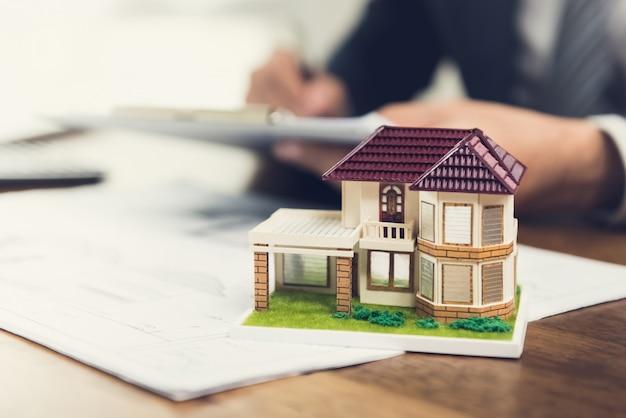 Casa modello su una scrivania con planimetrie per un progetto Foto Premium
