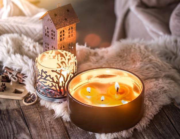 Casa natura morta all'interno con belle candele, sullo sfondo di un arredamento accogliente Foto Gratuite