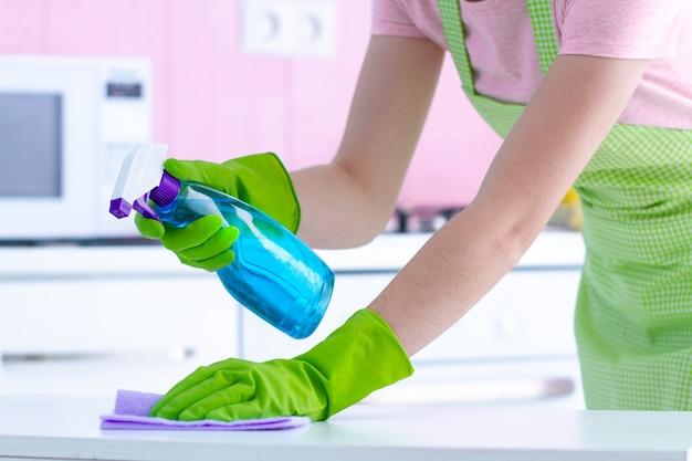 Casalinga in guanti di gomma protettivi che pulisce la polvere dal tavolo in cucina a casa con uno straccio e uno spray. Foto Premium