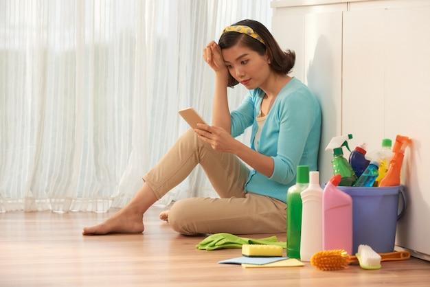 Casalinga seduta sul pavimento della cucina prendendo una pausa dalle faccende domestiche e utilizzando smartphone Foto Gratuite