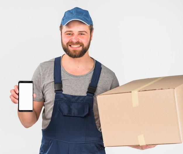 Casella e smartphone della tenuta del fattorino con lo schermo in bianco Foto Gratuite