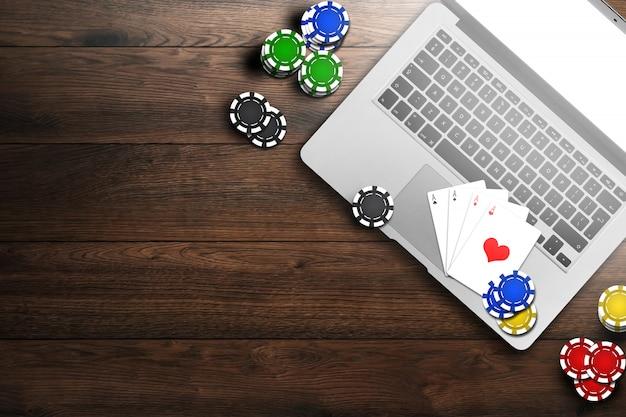 Casinò online, laptop, carte con fiches su legno Foto Premium