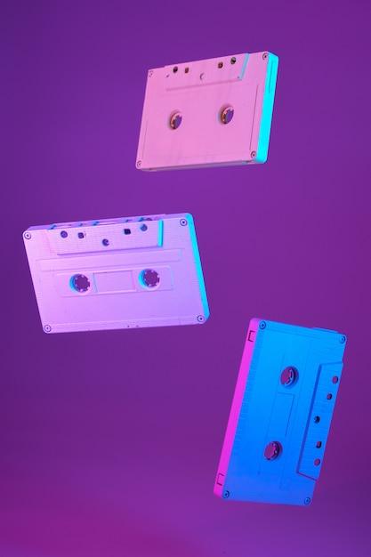 Cassetta a nastro stile vintage sospeso in aria su sfondo viola Foto Premium