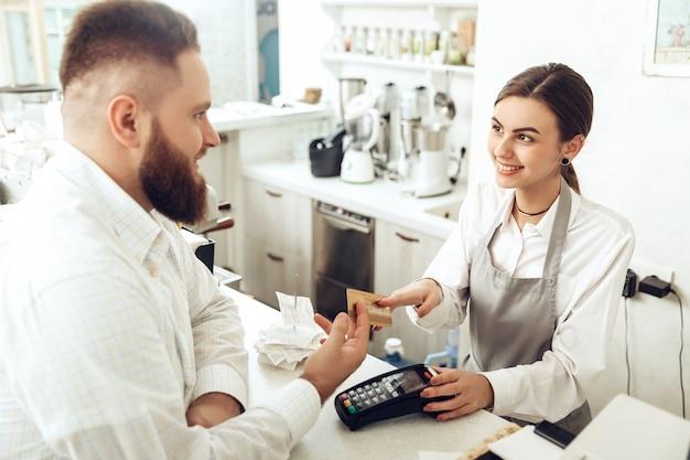 Cassiere allegro utilizzando il dispositivo digitale per il pagamento Foto Premium