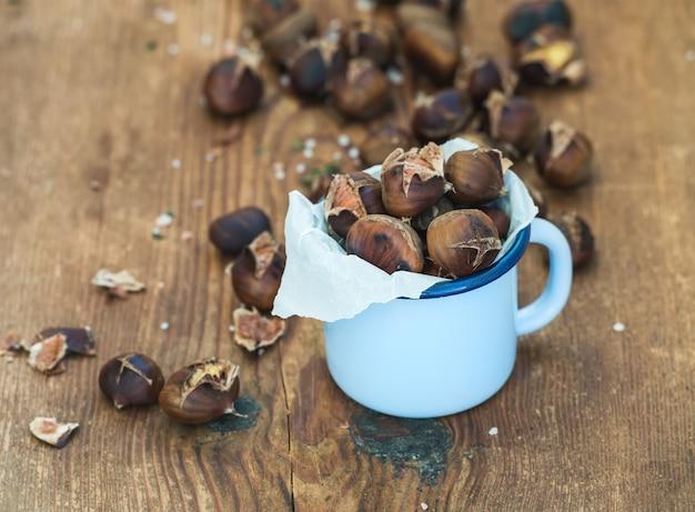 Castagne arrostite in tazza blu dello smalto sul fuoco di legno e selettivo rustico. Foto Premium