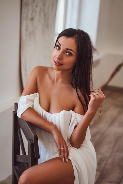 Castana sexy in vestito bianco che si siede vicino alla finestra Foto Premium