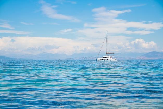 Catamarano al mare blu. catamarano della barca a vela sull'oceano vicino alla spiaggia. Foto Premium