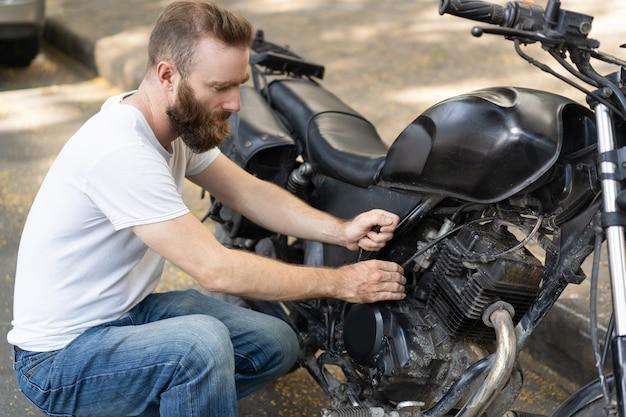 Cavaliere messo a fuoco che prova a rianimare motocicletta rotta Foto Gratuite
