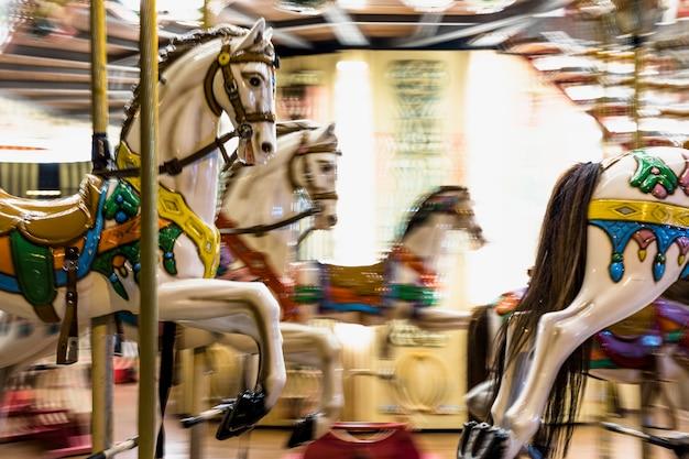 Cavalli giocattolo su un carosello vintage tradizionale fiera Foto Gratuite