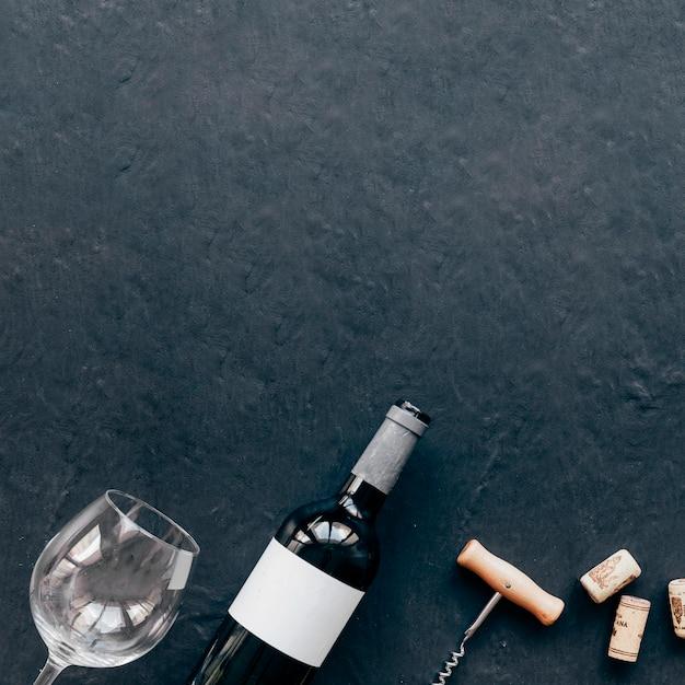 Cavatappi e bicchiere vuoto vicino alla bottiglia Foto Gratuite