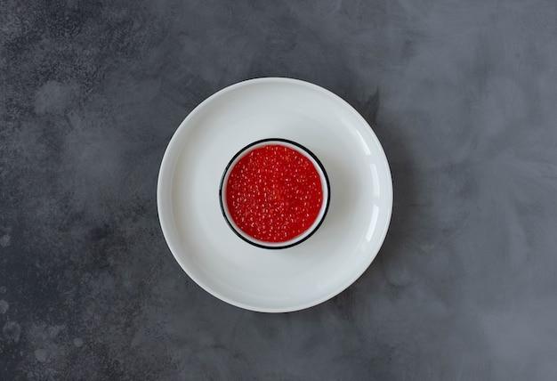 Caviale rosso in un piatto bianco su uno sfondo scuro. vista dall'alto. copia spazio Foto Premium