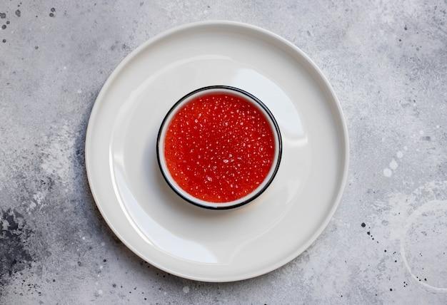 Caviale rosso in una ciotola bianca su sfondo chiaro Foto Premium