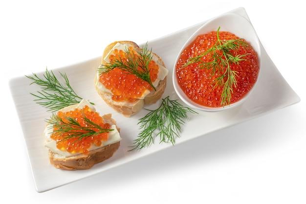 Caviale rosso sul pane con burro ed erbe. cibo salutare. antipasto di pesce. isolato Foto Premium