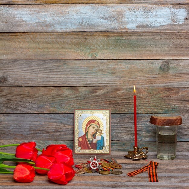 Celebrazione delle medaglie del giorno della vittoria, icona ortodossa e candela rossa accesa, bouquet di fiori di tulipani rossi e un bicchiere di vodka con un pezzo di pane di segale Foto Premium