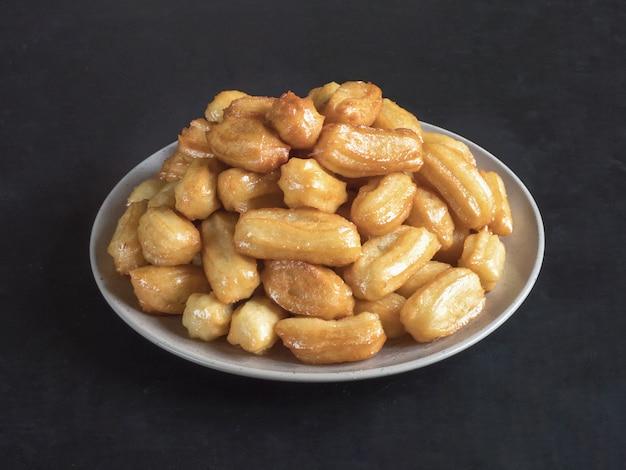 Celebrazione di dolci arabi eid ramadan. dessert turco tradizionale tulumba - tulumba tatlisi. Foto Premium