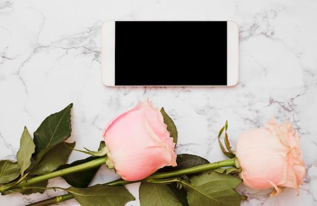 Cellulare con due rose rosa su sfondo di marmo Foto Gratuite