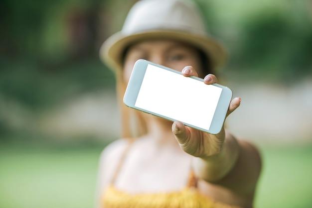 Cellulare della tenuta della mano della donna, smartphone con lo schermo bianco Foto Gratuite