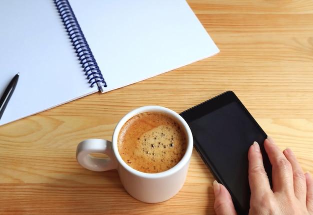 Cellulare della tenuta della mano della femmina accanto ad una tazza di caffè caldo con il taccuino e penna sullo scrittorio funzionante Foto Premium