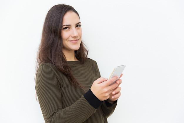 Cellulare latino sorridente contento della tenuta della donna Foto Gratuite