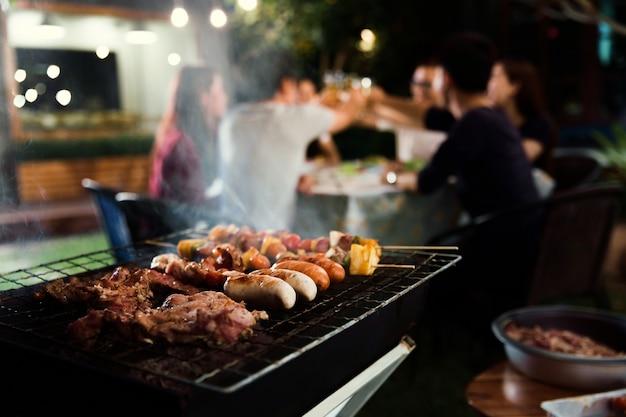 Cena, barbecue e arrosto di maiale di notte Foto Premium