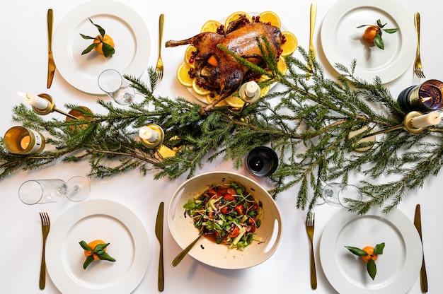 Cena festiva natalizia. pasto tradizionale delizioso di festa e mani delle persone che li mangiano. tavolo decorato con gustosi piatti. flat ley. tavolo bianco Foto Premium