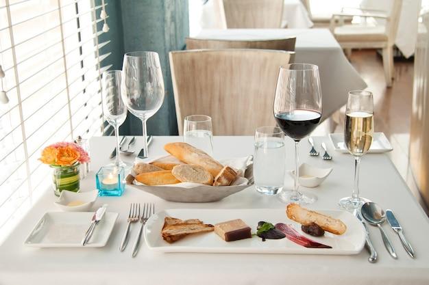 Cena impostata su tavola bianca, set completo di lusso di cena francese Foto Gratuite