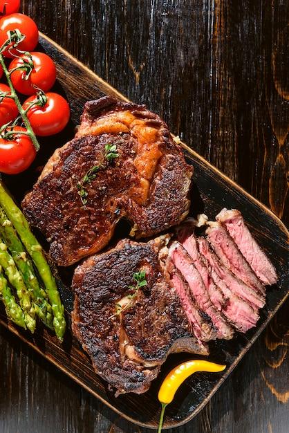 Cena per due deliziose bistecche succose, asparagi con parmigiano e verdure. Foto Premium