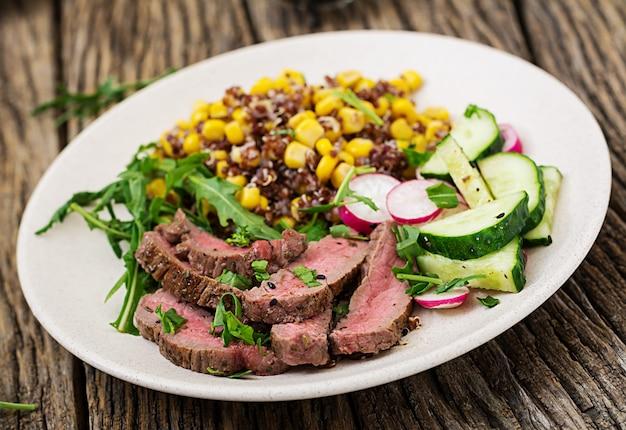 Cena salutare. prepara il pranzo con bistecca di manzo alla griglia e quinoa, mais, cetriolo, ravanello e rucola sul tavolo di legno. insalata di carne. Foto Gratuite