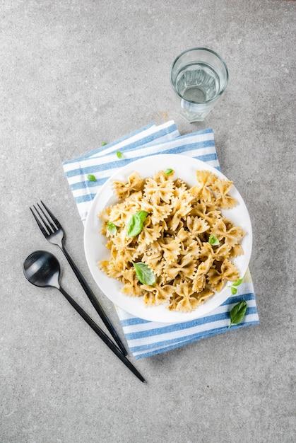 Cena vegana. pasta di farfalle con salsa di pesto e foglie del basilico sul fondo di pietra grigio del piatto bianco Foto Premium